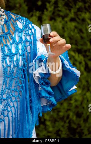 Spanish woman holding glass of fino sherry, Fuengirola Feria, Costa del Sol, Andalucia, Spain, Europe, - Stock Image