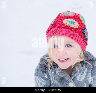 Happy toddler with colourful beanie - Stock Image