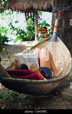 Thailand, Nong Khai, Nong Khai. A woman relaxes with a book in a woven rattan hammock. - Stock Image