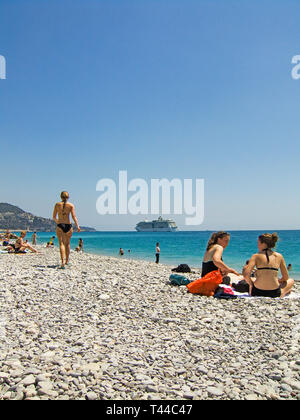 Nice Cote dAzur France - two girls on the Promenade des Anglais beach watching a cruise ship passing. - Stock Image