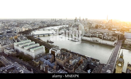 The River Thames passes through the Centre of London with the Touristic District Big Ben and Iconic Riverside Observation Wheel on opposite sides - Stock Image