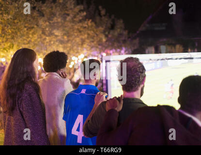 Friends watching soccer match on projection screen in backyard - Stock Image