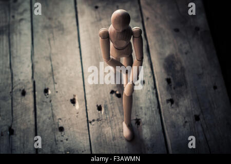 Wooden figurine standing on an old wooden table. - Stock Image