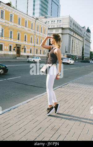 Beautiful blonde girl posing for the camera in an urban contest with city building in the background - Stock Image