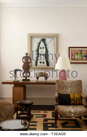 Modern art by leopard print chair in living room - Stock Image