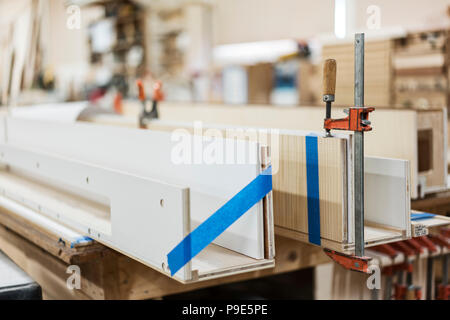 Close up of small bar clamps being used in a woodworking factory. - Stock Image