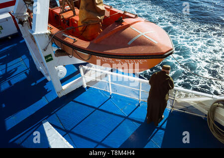 A Moroccan man wearing a djellaba looks at the sea water from the deck of a ferry boat crossing the Gibraltar Strait betwen Tanger, Morocco, and Algec - Stock Image