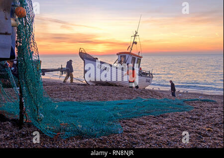 Hastings, East Sussex, UK. Hastings fishing boat being launched at sunrise. Hastings has the largest beach-launched fishing fleet in Europe. - Stock Image