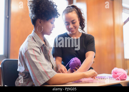 Smiling women doing string art project - Stock Image