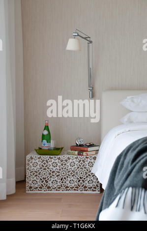 Table and light by bed in modern bedroom - Stock Image
