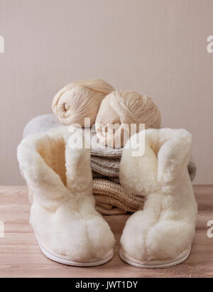 Pair of warm winter sheepskin slippers (alpaca), wool yarn  on a pile of warm woolen clothes (Selective focus) - Stock Image
