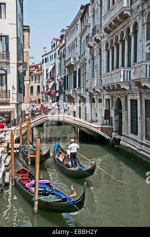 Bridge over canal Rio de la Canonica and gondalas with godalier and sunshine Venice Italy - Stock Image