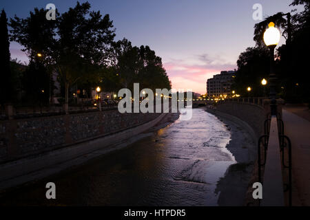 Granada Spain River Genil at night meandering through Plaza de Humillaredo with the street lights against the dusk - Stock Image