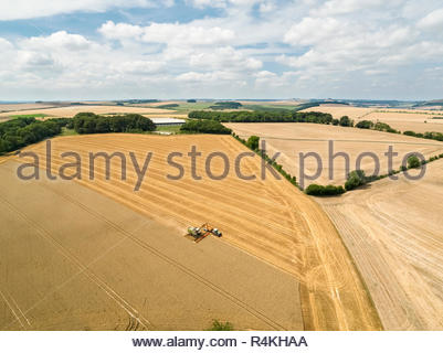 Harvest aerial landscape of combine harvester cutting summer wheat field crop with tractor trailer on farm - Stock Image