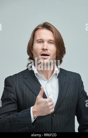 The handsome men in black suits on a white background, a white shirt, brutal man with long curly hairs, business man, very stylish, portrait, emotions - Stock Image