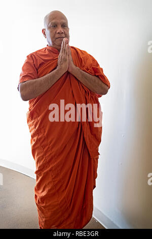 Posed portrait of a Buddhist monk from Sri Lanka outside the New York Buddhist Vihara Association in Queens Village, Queens, New York City. - Stock Image