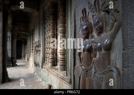 Corridor with dancers carved onto stone wall in Angkor Wat. The Angkor Wat complex, Built during the Khmer Empire age, located in Siem Reap, Cambodia, - Stock Image