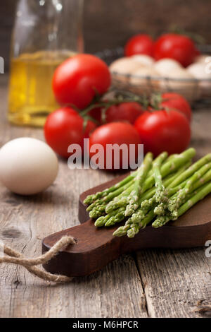 ingredients for a healthy breakfast. fresh asparagus on a cutting board, tomatoes, eggs on old wooden background - Stock Image