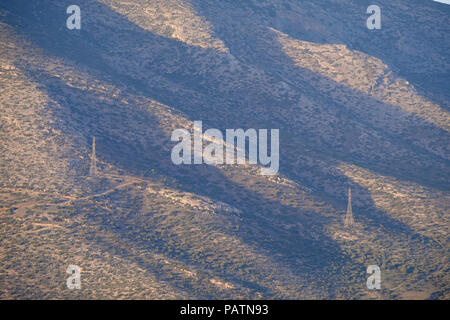 Lagonissi ( Lagonisi ) mountain side, shadowed ridges with power line towers carrying electricity. East Attica, Greece, Europe. - Stock Image