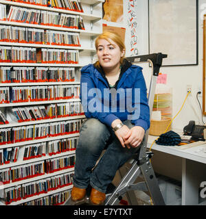 Woman sitting on ladder in stockroom - Stock Image