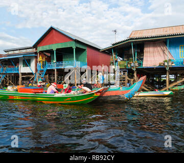 Traders visiting Kampong Phluk floating village on Kampong Phluk River Siem Reap Cambodia Asia in canoes selling fresh fish to inhabitants of stilted  - Stock Image