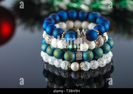 Exquisite women's bracelets made of natural stones, agate and sugar quartz with accessories that are encrusted with cubic zirconias. Close-up. Studio  - Stock Image