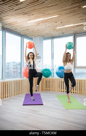 Two young slim women doing exercises holding a ball in the fitness studio - Stock Image