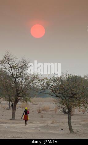 Africa, Namibia, Opuwo. Himba woman walking at sunset. Credit as: Wendy Kaveney / Jaynes Gallery / DanitaDelimont.com - Stock Image