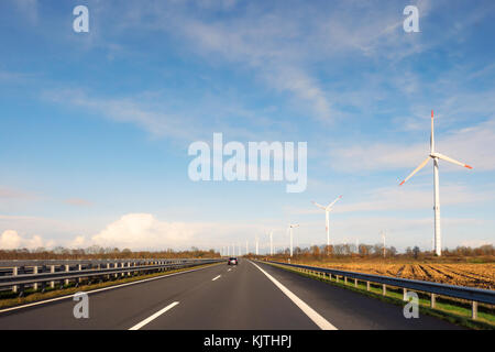 Windmills along highway A31 near the city of Leer, Germany on a sunny day. Seen from the driver's perspective. - Stock Image