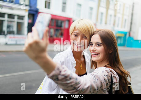 Young women friends taking selfie with smart phone on urban street - Stock Image