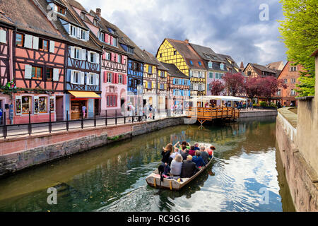 Colmar, France. Boat with tourists on canal in Little Venice (la Petite Venise) area - Stock Image
