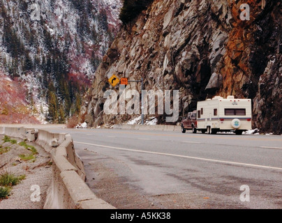 A truck pulling a camper trailer up highway 2 known as Stevens Pass 2003 - Stock Image