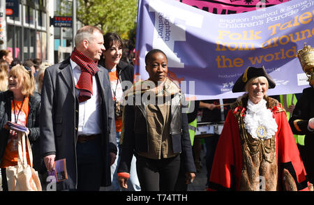 Brighton UK 4th May 2019 - Rokia Traore (centre) leads thousands of schoolchildren , teachers and parents taking part in the annual Brighton Festival Children's Parade through the city which has the theme 'Folk Tales from Around the World' . Organised by the Same Sky arts group the parade traditionally kicks off the 3 week arts festival with this years guest director being the singer songwriter Rokia Traore . Credit : Simon Dack / Alamy Live News - Stock Image