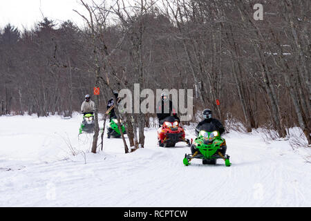 Four snowmobiles riding on a groomed trail along the Sacandaga River Valley near Speculator, NY USA - Stock Image