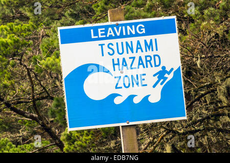 Blue and white corrugated PVC sign on wooden post with lettering 'Leaving Tsunami Hazard Zone' posted along - Stock Image