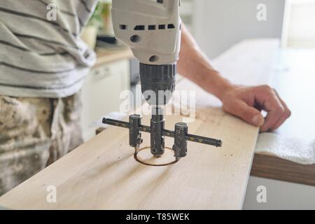 Close-up of carpenters hand using professional woodworking electric tools when working with wood. Male carving hole in wooden panel board, carpentry,  - Stock Image