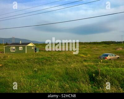 Rural area of Sally's Cove with one house and car in long grass - Stock Image