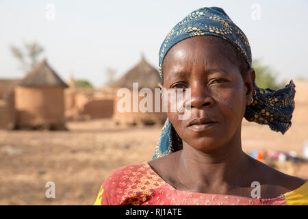 Kourono village, Yako province, Burkina Faso; A portrait of a woman with tribal marking on her face, in front of village grain stores. - Stock Image