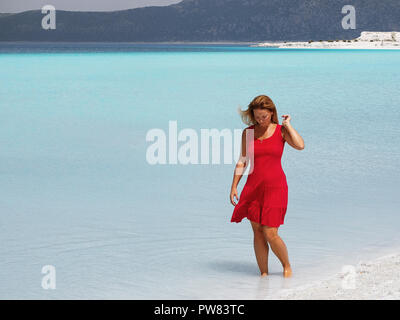 Lady in red dress walking inside of Salda Lake. Isparta. Turkey - Stock Image