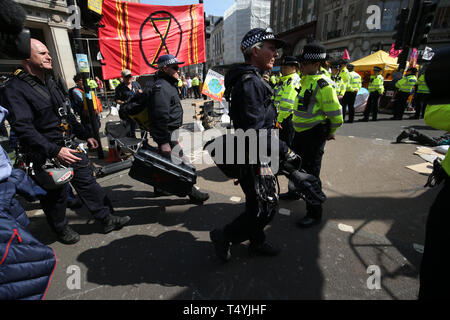 Police arrive carrying equipment as Extinction Rebellion protests continue in Oxford Circus, London. - Stock Image