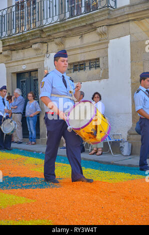 Annual Corpus Christi Parade on streets covered in flower petal design. Adult drummer. Ponte de Lima, Portugal, June 15, 2017 - Stock Image