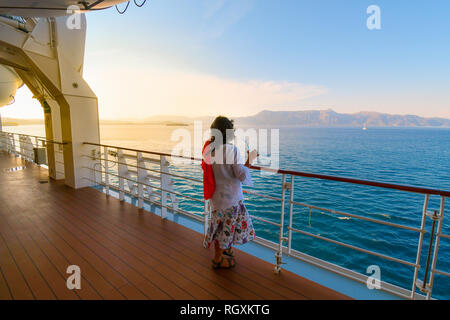A woman sips a drink on the deck of a cruise ship as the sun sets and the ship passes islands on the Aegean Sea - Stock Image