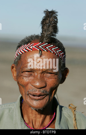 Elderly Bushman wearing beaded headband and ostrich feather - Stock Image