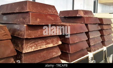 Many different big chocolate bars stacked on confectionery shelves - Stock Image