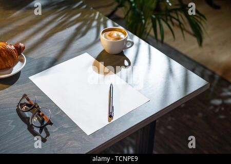 Close up of white coffee cup, croissant, glasses, blank sheet of paper and pen on dark wooden table with tropic plant on background. - Stock Image
