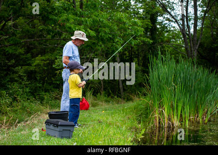 A grandfather and grandson fish next to a pond during the summer. - Stock Image