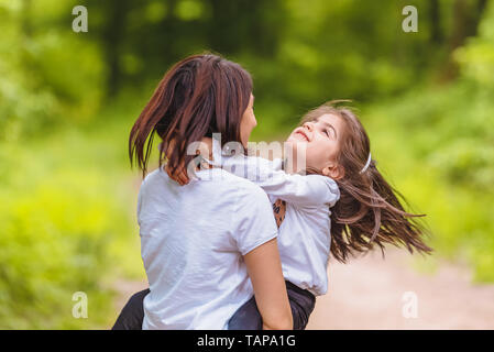 Young mom holds and spins her little girl in forest.Happy mother and daughter moments with love and natural emotion.Photo of young mother and her daug - Stock Image