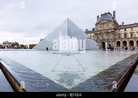Paris (France) - View of famous Louvre Museum and Pyramid in a winter and rainy day - Stock Image
