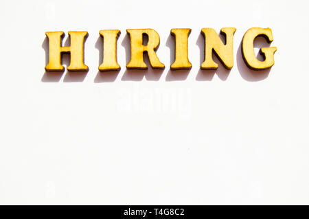 The word hiring is written in gold letters, isolated on white background, copy space, mockup for designer. - Stock Image