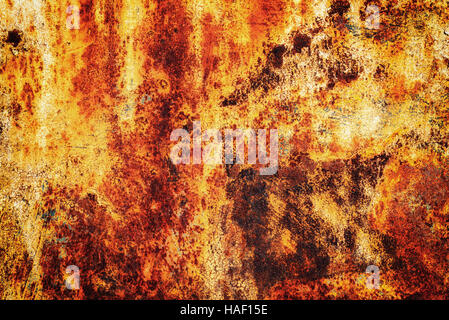 Bright orange rust on a metallic surface with peeling specks of flaking metal - Stock Image
